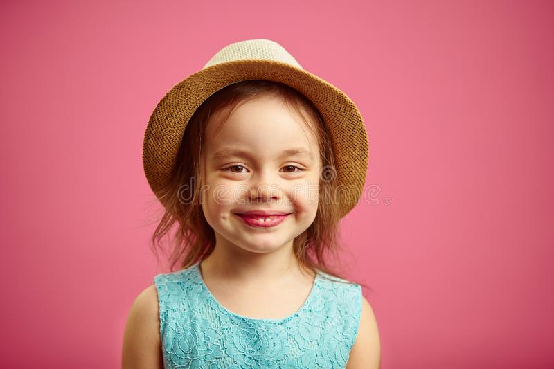 Portrait of beautiful little girl with straw hat and blue dress, stands on pink . stock photos