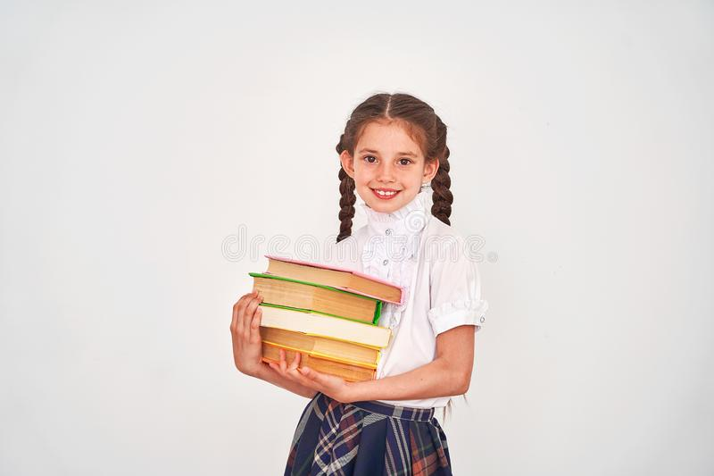 Portrait of a beautiful little girl student with a backpack and a stack of books in his hands smiling on a white background stock photos