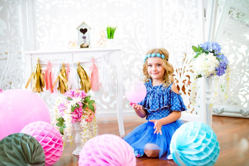 A portrait of a beautiful little girl in a studio decorated many color balloons. A portrait of a beautiful little girl laughs in a studio decorated many color royalty free stock photography