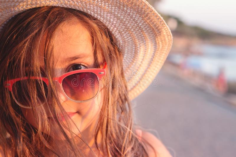 Portrait of a beautiful little girl with sunglasses and straw hat on the beach royalty free stock photo