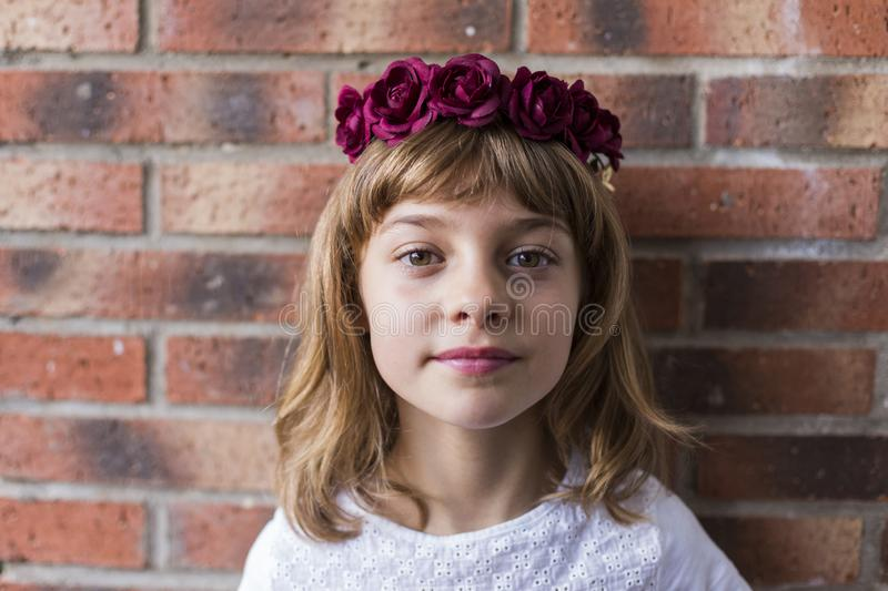 Portrait of a beautiful little girl wearing a red crown roses on her head. Brick background. Lifestyle. Wreath, fashion, young, happy, flower, white, spring royalty free stock photography