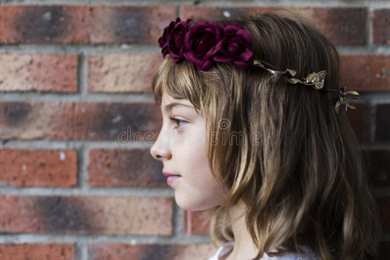 Portrait of a beautiful little girl wearing a red wreath roses on her head. Brick background. Lifestyle. Fashion, young, happy, flower, white, spring, bouquet royalty free stock images