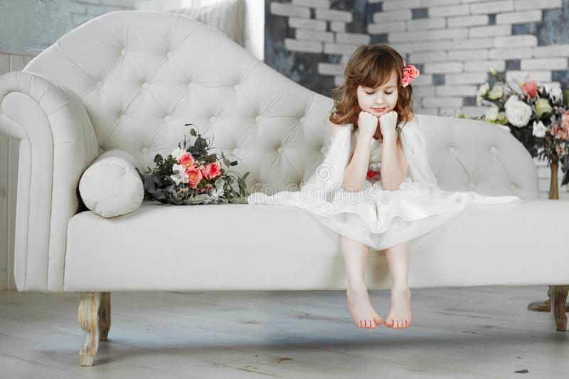 Portrait of beautiful little girl in white dress on white sofa stock photos