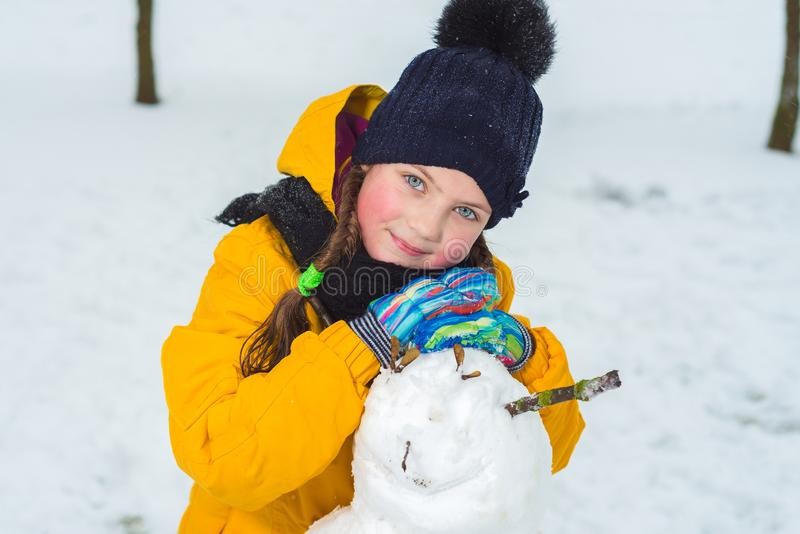 Portrait of a beautiful little girl in winter. happy child makes a snowman. royalty free stock photography