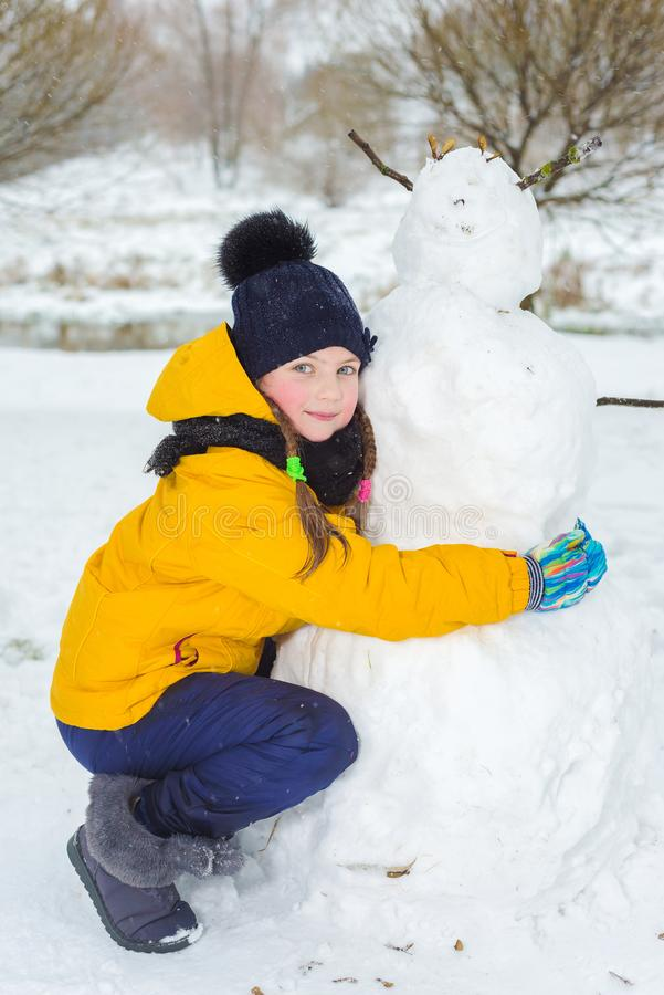 Portrait of a beautiful little girl in winter. happy child makes a snowman. royalty free stock photos