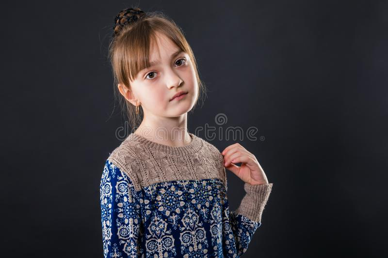 Portrait of little schoolgirl on a dark background stock photo