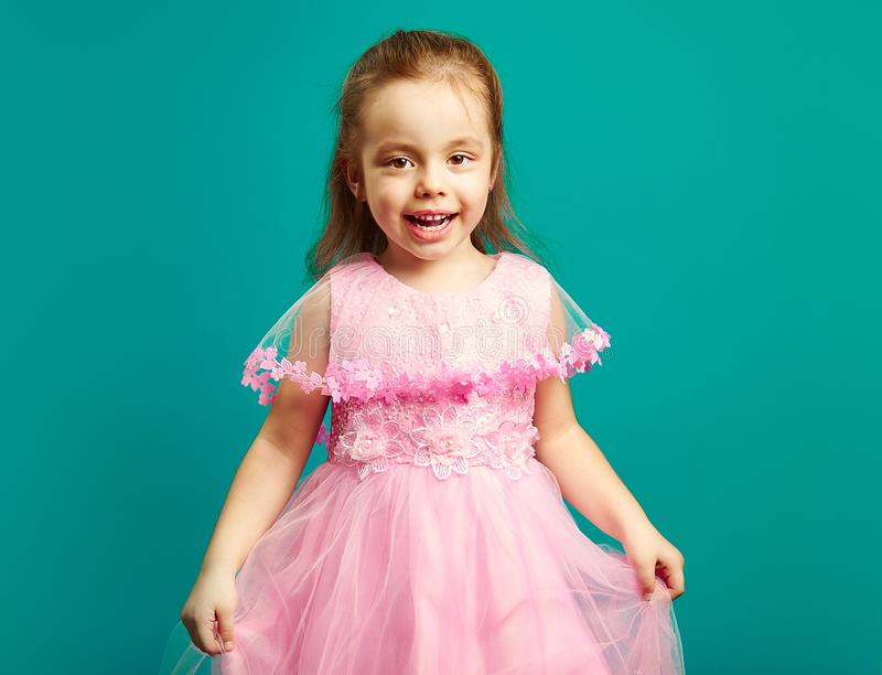Beautiful little girl in pink dress on blue background. stock image