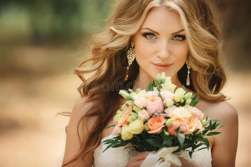 Portrait of beautiful luxury bride with roses wedding bouquet outdoors. Young woman with professional make up and hair style. Wedding day. Marriage royalty free stock image