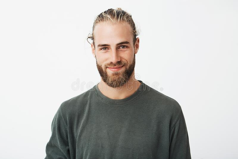 Portrait of beautiful mature blonde bearded guy with trendy hairdo in casual grey shirt smiling and looking in camera. royalty free stock photo