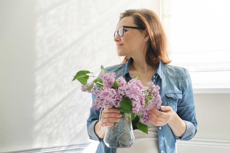 Portrait of beautiful mature woman at home with bouquet of lilac flowers. Background of home interior dining near the window royalty free stock photo
