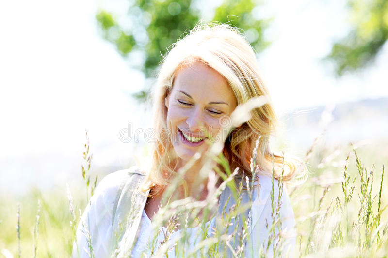 Portrait of beautiful mature woman standing in meadow royalty free stock photo