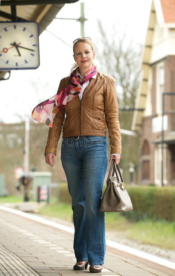 Portrait of a beautiful mature woman standing on train station platform. Outdoors stock image