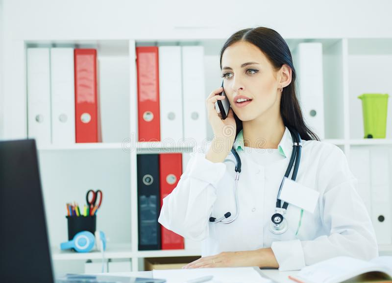 Beautiful medical doctor talking on the phone looking at laptop screen in the office. Portrait of a beautiful medical doctor talking on the phone in the office royalty free stock photo