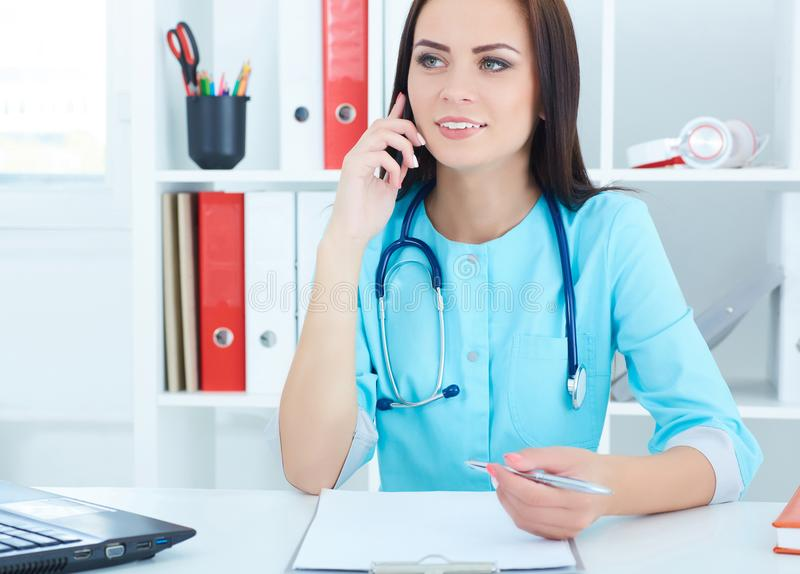 Portrait of young beautiful medical doctor talking on the phone. Portrait of a beautiful medical doctor talking on the phone stock photo
