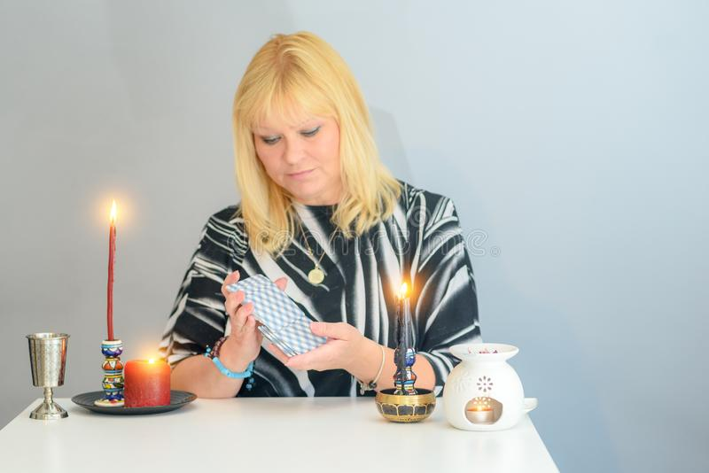 Portrait of beautiful middle age woman sits near a fortune teller desk with a tarot cards and candles. Middle age beautiful woman sits near a fortune teller royalty free stock image