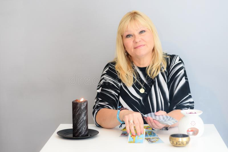 Portrait of beautiful middle age woman sits near a fortune teller desk with a tarot cards and candles. stock image