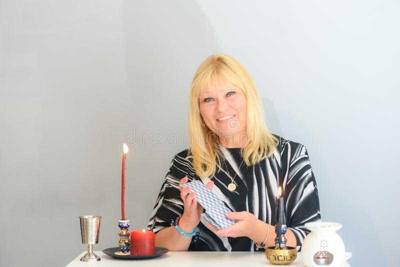 Portrait of beautiful middle age woman sits near a fortune teller desk with a tarot cards and candles. Middle age beautiful woman sits near a fortune teller royalty free stock photos