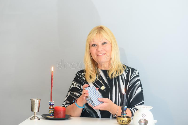 Portrait of beautiful middle age woman sits near a fortune teller desk with a tarot cards and candles. Middle age beautiful woman sits near a fortune teller stock photo