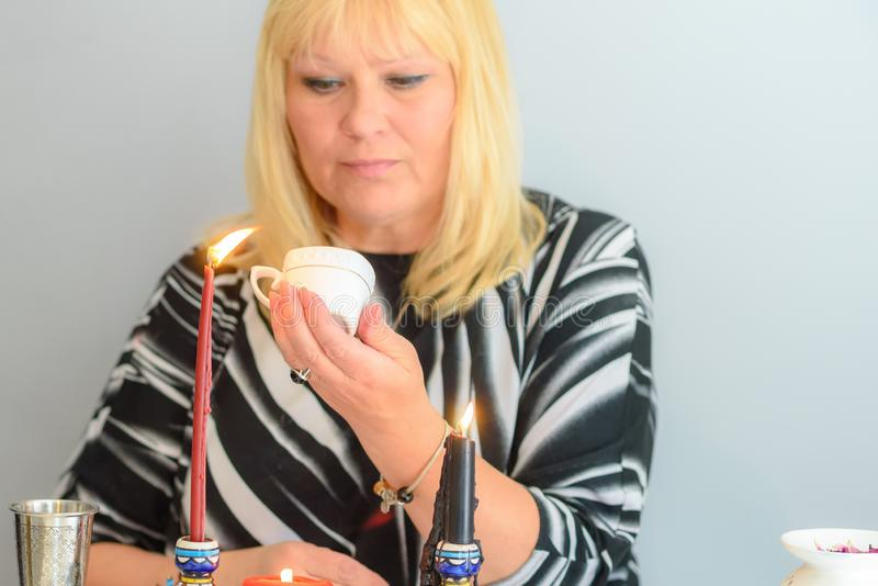 Portrait of beautiful middle age woman sits near a fortune teller desk with a tarot cards and candles. Middle age beautiful woman guessing on the coffee grounds stock images