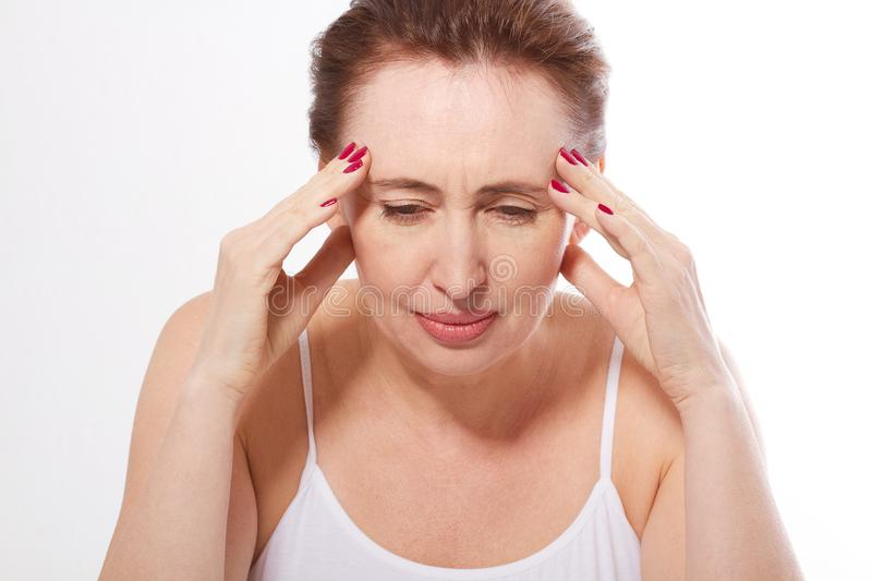 Portrait of beautiful middle aged brunette woman with headache on white. Migraine, menopause and stress. Copy space and m royalty free stock photography