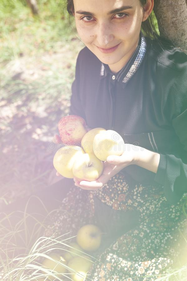 Autumn portrait. Portrait of beautiful middle-eastern woman at apple garden. Young female posing at the nature with freshly picked. Portrait of beautiful middle royalty free stock photo