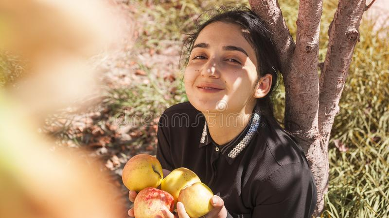 Autumn portrait. Portrait of beautiful middle-eastern woman at apple garden. Young female posing at the nature with freshly picked. Portrait of beautiful middle stock photos