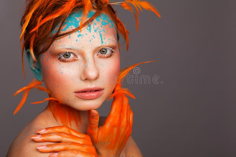 Portrait of a beautiful model with creative make-up and hairstyle using orange feathers royalty free stock photos