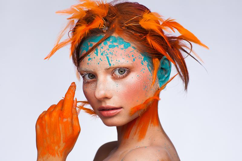 Portrait of a beautiful model with creative make-up and hairstyle using orange feathers stock photography