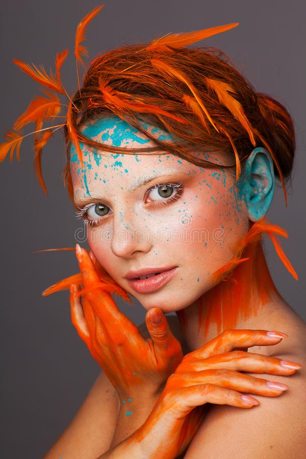 Portrait of a beautiful model with creative make-up and hairstyle using orange feathers stock image