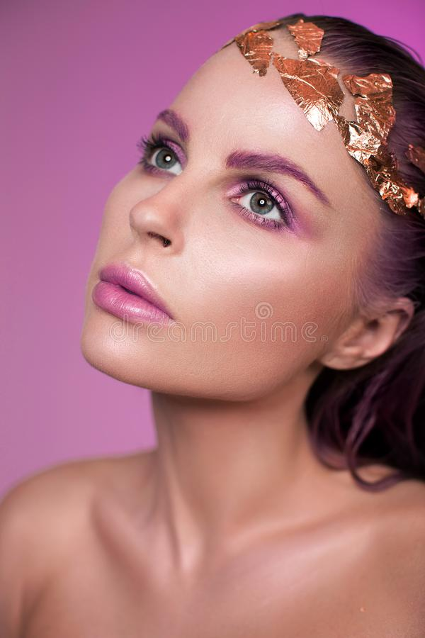 Portrait of a beautiful model with pink makeup. And pink wet hair. Blonde with clean skin royalty free stock images