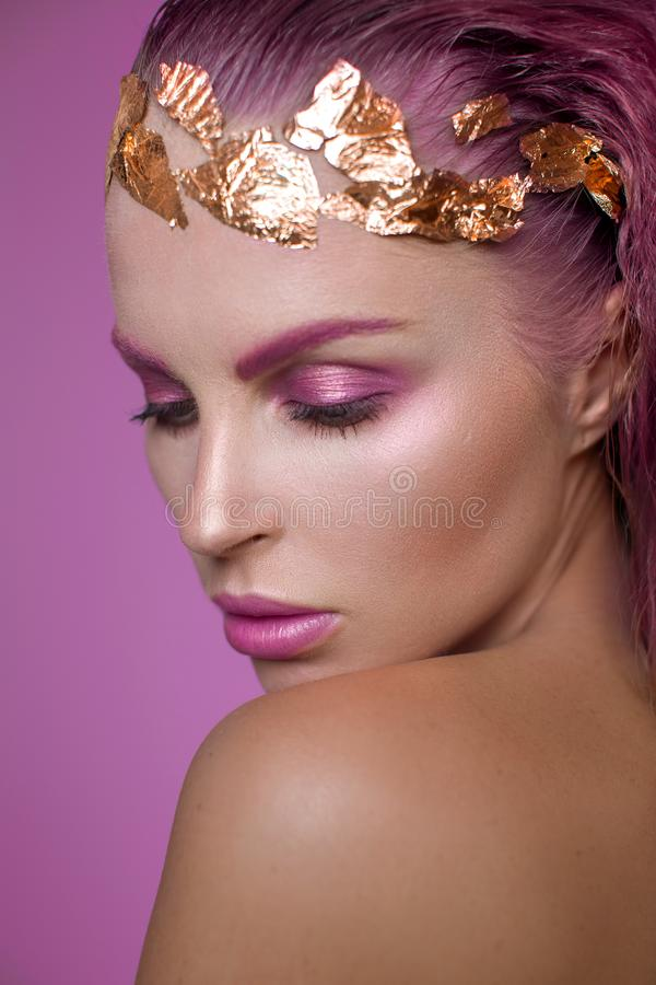 Portrait of a beautiful model with pink makeup. And pink wet hair. Blonde with clean skin royalty free stock photos