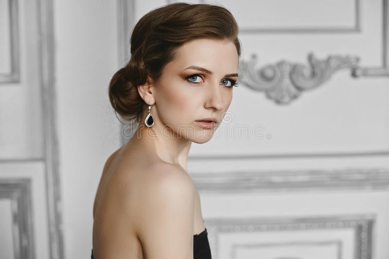 Portrait of beautiful model woman with trendy hairstyle and evening professional makeup. Side view of fashionable girl stock image