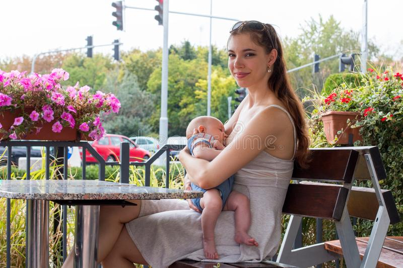 Portrait of pretty happy new mother breastfeeding hungry child in public, busy street on background. Young woman and happy new mother nursing her happy hungry royalty free stock photo