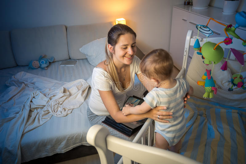 Portrait of beautiful mother taking baby out of crib at night royalty free stock photo