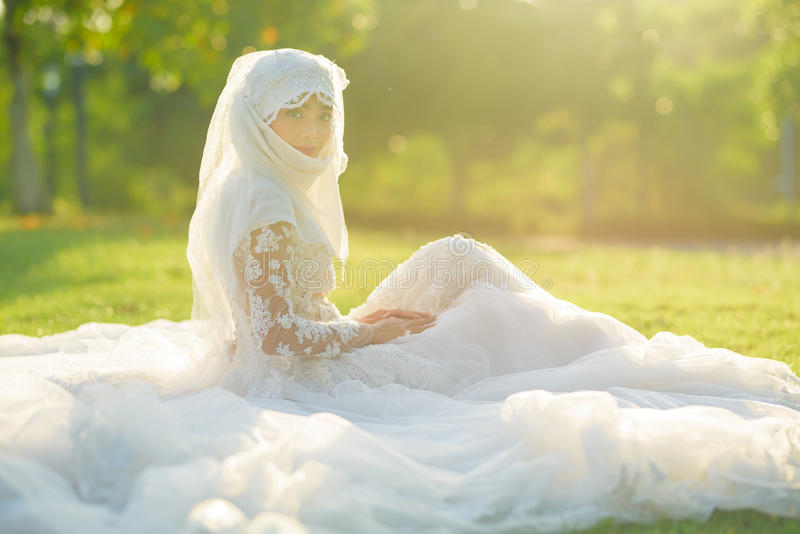 Portrait of a beautiful muslim bride with make up in white wedding dress with beautiful white headdress natural light. stock images