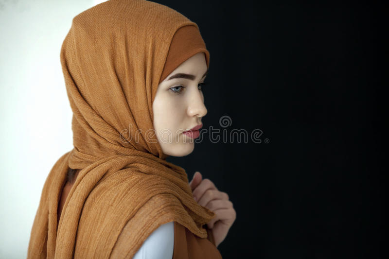 Portrait of a beautiful Muslim woman in a green scarf covering her head stock photography