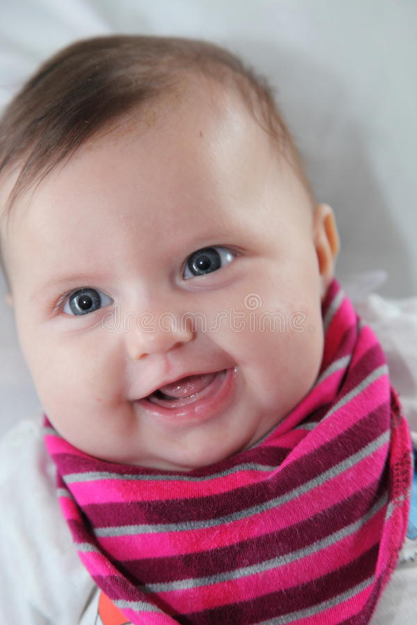 Portrait of a beautiful newborn baby. Portrait of a beautiful smiling newborn baby girl with a happy chubby cherubic face and look of contented innocence royalty free stock image