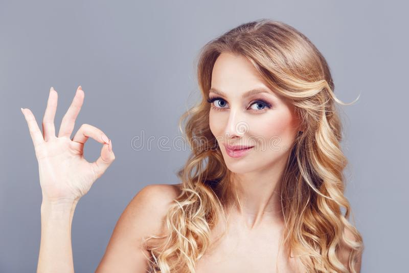 Portrait of beautiful nlondhair woman showing ok gesture and winking isolated over blue background royalty free stock photo