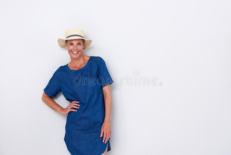 Beautiful older woman smiling with hat against white background. Portrait of beautiful older woman smiling with hat against white background royalty free stock photography