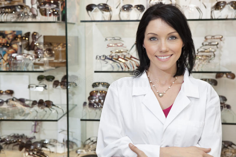Portrait of a beautiful optometrist with arms crossed in store stock photos