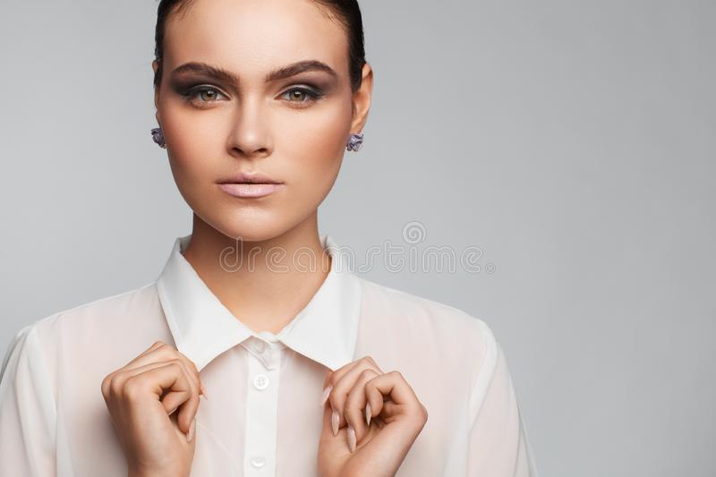 Portrait of a beautiful pacified woman in a white shirt. Studio photo session royalty free stock image