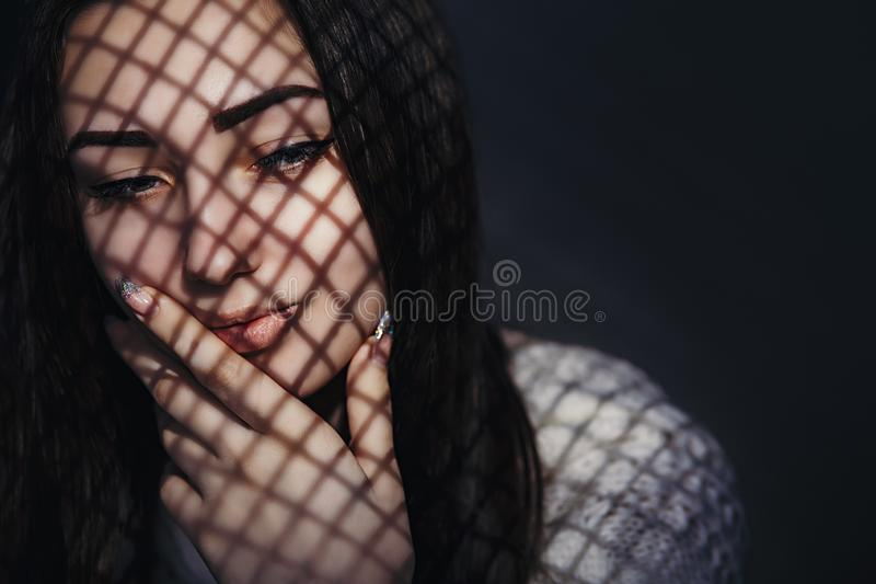 Portrait of beautiful pensive girl with a light pattern on the face in the form of a grid,young woman put her hand on her face royalty free stock photo