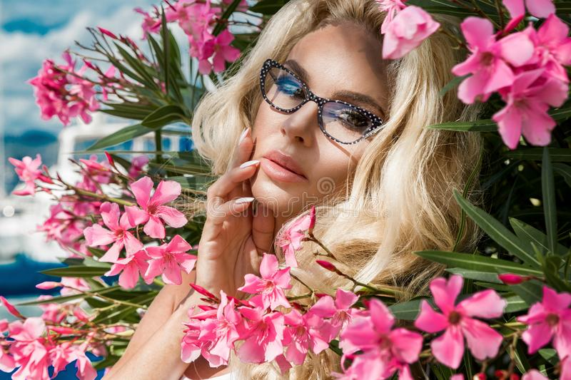 Portrait beautiful phenomenal stunning elegant blonde model woman with perfect face wearing a glasses stands with elegant out. Fit on amazing view with flowers royalty free stock photography