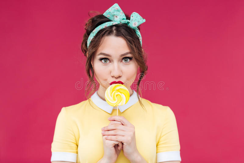 Portrait of beautiful pinup girl eating sweet yellow lollipop royalty free stock photo