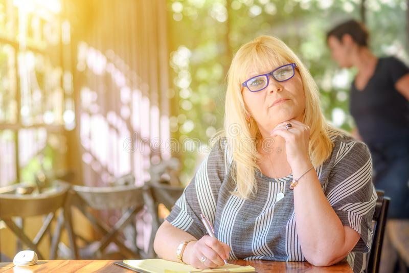 Portrait elegant middle aged plus size woman sitting and making notes to her diary on balcony or terrace of cafe. royalty free stock photo