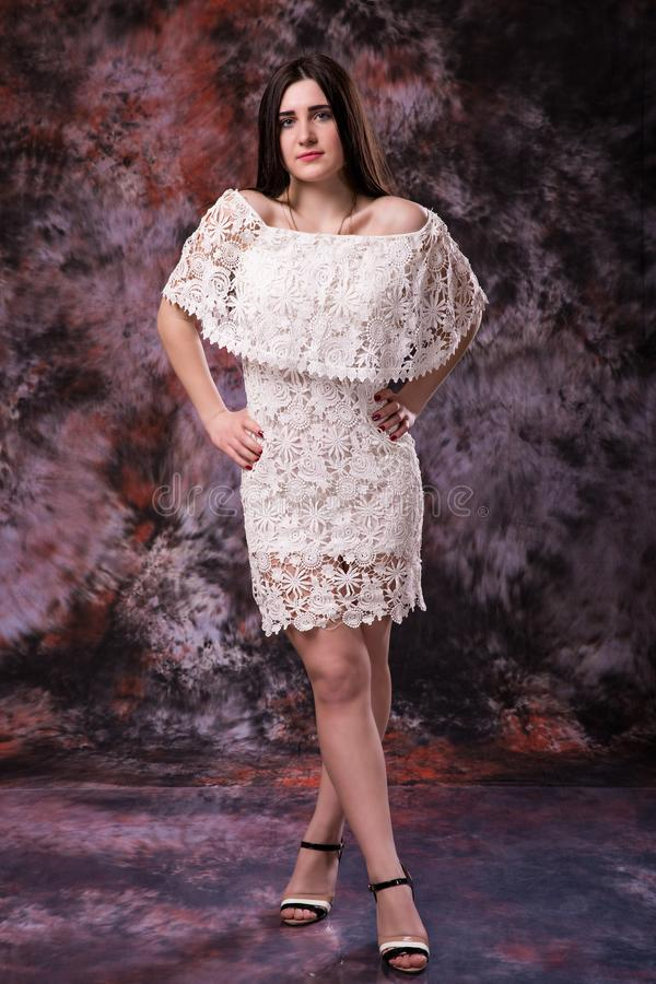Portrait of beautiful plus size curly young woman in white dress posing on marble colored background stock photos
