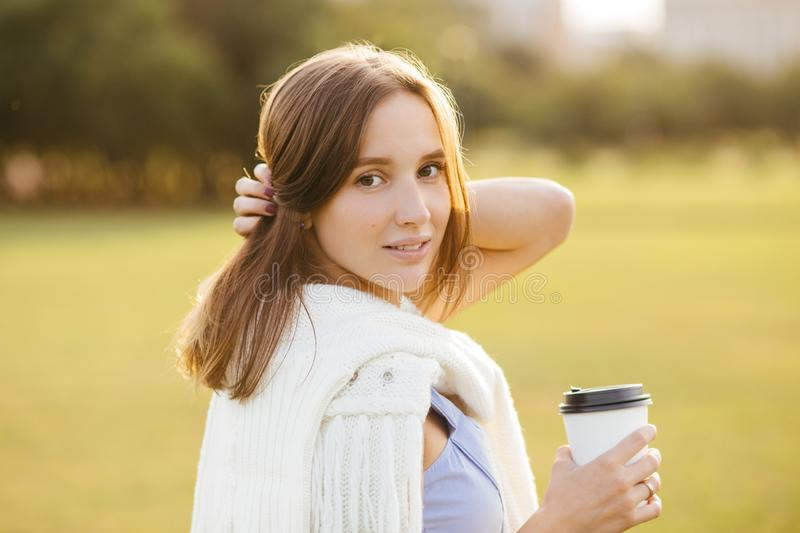 Portrait of beautiful pretty female with dark hair, healthy pure skin, dressed in casual outfit, drinks takeaway coffee, poses out royalty free stock photography