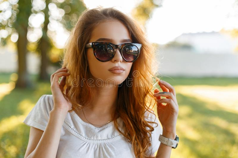 Portrait of a beautiful pretty young redhead hipster woman in trendy sunglasses in a white t-shirt outdoors. Attractive girl model royalty free stock image