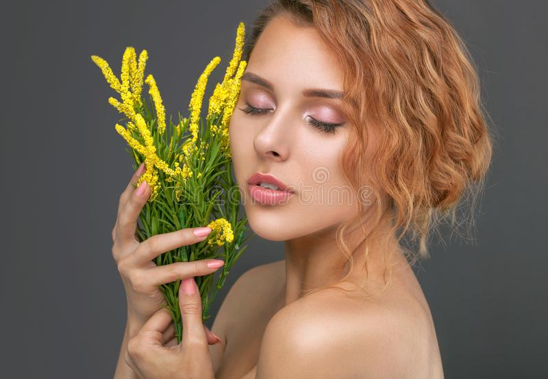 Portrait of a beautiful red-haired curly woman with fresh nude make-up, thick eyebrows and with clean skin,she holds yellow. Flowers near her face. Face close royalty free stock photo
