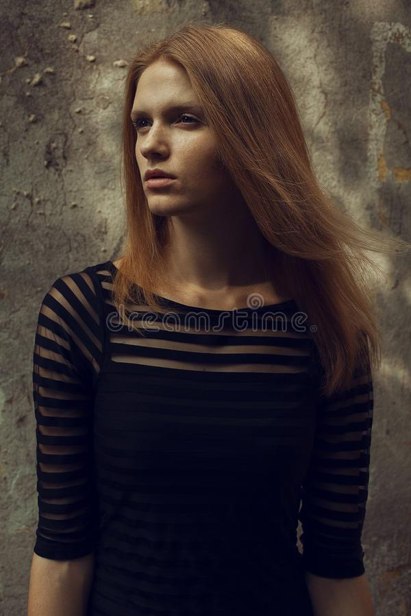 Portrait of a beautiful red-haired ginger model with freckles on her face posing in a black cocktail dress over old house` wall royalty free stock photos